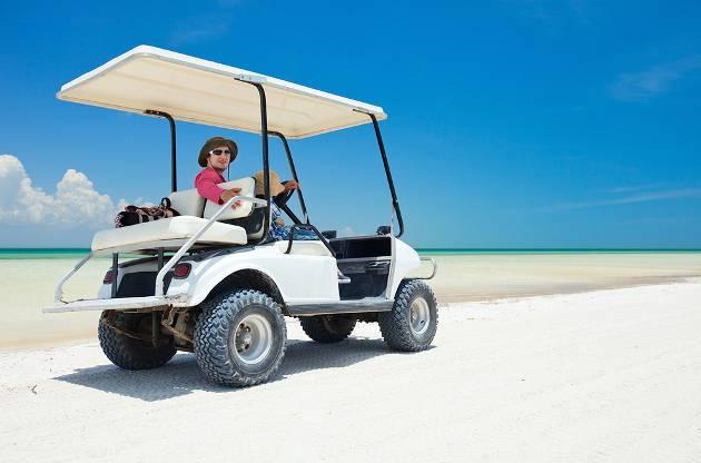 Driving a gofl cart along a tropical beach