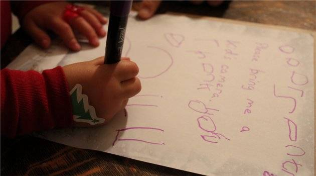 small child writing letter to santa
